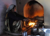 Indian woman cooking over an open fire