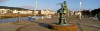 Whitehaven harbour - Sculpture of lookout boy with telescope sitting on capstan,